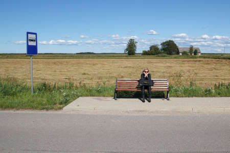 tourists stop: lonely woman waiting for a bus in rural area Stock Photo