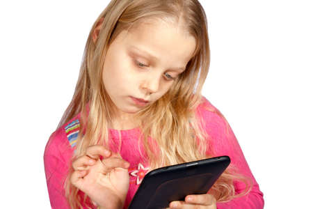 little girl using ebook reader or digital tablet computer photo