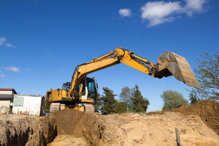 excavator digging sewer trenche in construction site Stock Photo