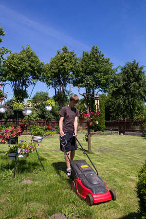 Boy mowing the garden with an electric lawn mower Stock Photo