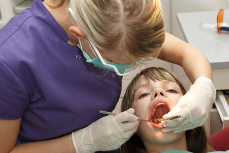 dentists: dentist check young girl teeth