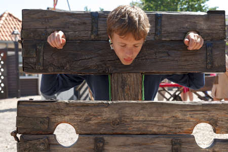 a boy trapped in a medieval torture device