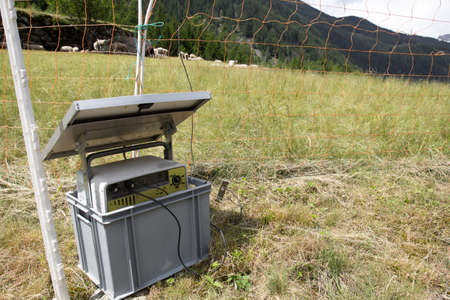 elektrischer Zaun: Solarenergie-Panel mit elektrischen Zaun in Schweizer Alpen Lizenzfreie Bilder
