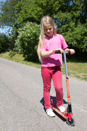 little girl rides a scooter on a rural road photo