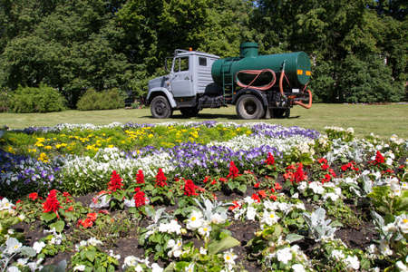 City park with a large flower bed and watering car