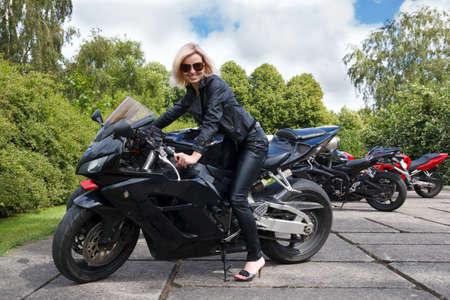 motociclista: biker sonriente niña vestida con ropa de cuero en una motocicleta Foto de archivo