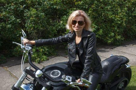 motociclista: mujer sonriente vestida con ropa de motorista de cuero en una motocicleta Foto de archivo