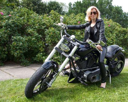 moteros: biker sonriente ni�a vestida con ropa de cuero en una motocicleta Foto de archivo