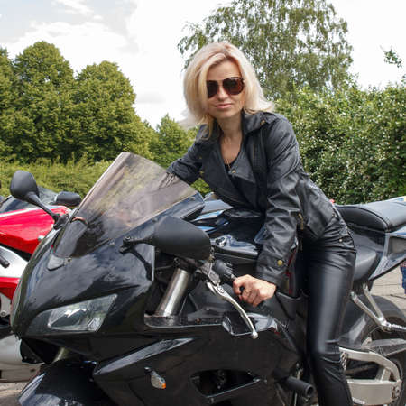 smiling biker girl dressed in leather clothes on a motorcycle photo