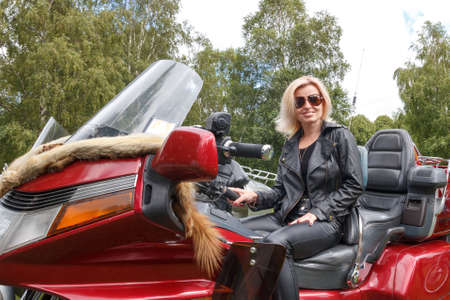 Woman dressed leather clothes on a big red motorcycle photo