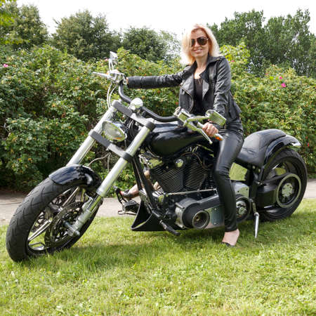 Woman dressed leather clothes on a big motorcycle photo