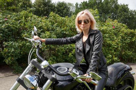 mujer sola: Mujer vestida de ropa de cuero a una motocicleta grande