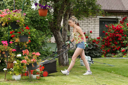 Woman mows the garden with electric mower
