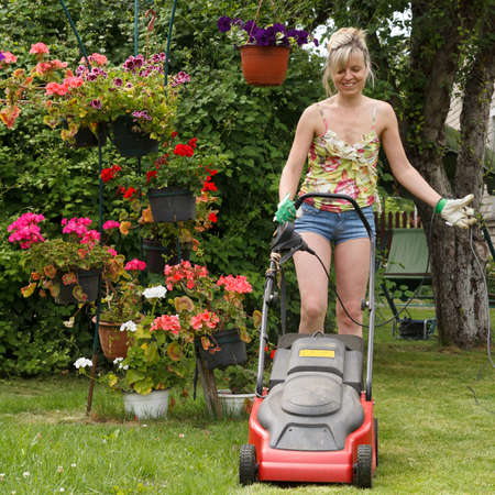 mows: Woman mows the lawn with an electric lawn mower