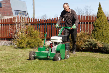 Lawn Aerator.A lawn aerator is a garden tool or machine designed to aerate the soil in which lawn grasses grow Stock Photo - 22117215