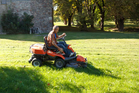 man driving a red lawn mower (tractor) in the city park photo