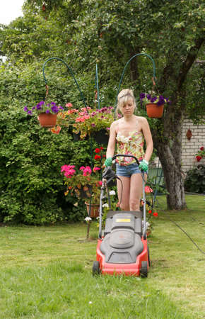 Woman cut the flower garden with an electric mower photo