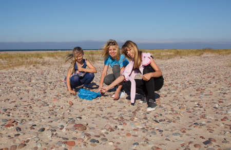 Three smiling girls on an empty beach collect stones
