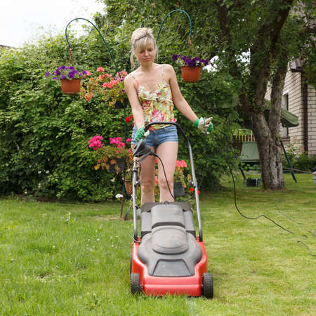 Woman mowed grass in a flower garden photo