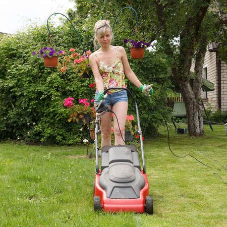 Woman mowed grass in a flower garden