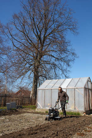 motor hoe: Spring Garden work. man working with Garden Tiller