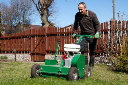 Spring work in garden. Man work with Man working with Lawn Aerator Stock Photo