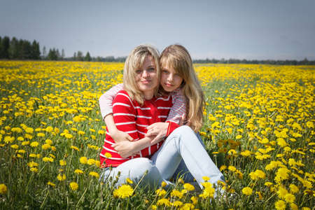 mother with daughter in dandelion field photo