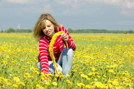 smiling woman make dandelion wreath in meadow photo