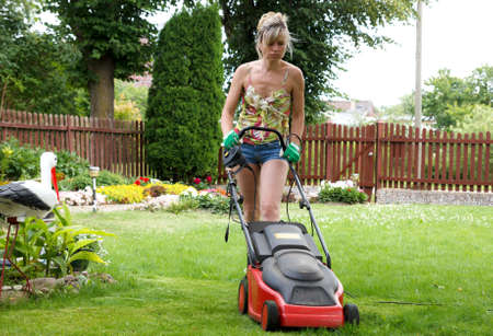 Woman cuts the grass with an electric lawn mower photo