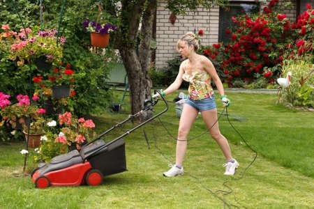 резка: Женщина режет траву с электрическим газонокосилки Фото со стока