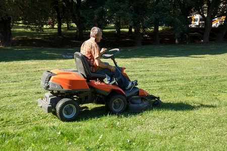 mow: man on tractor mow the grass in the city park