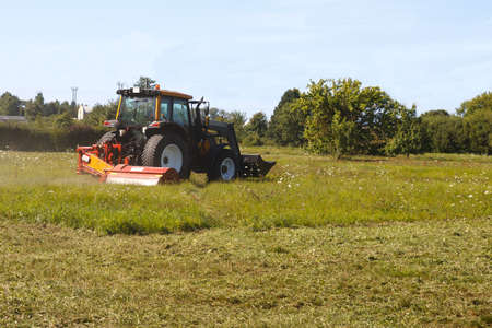 mows: tractor mows the lawn in suburban field