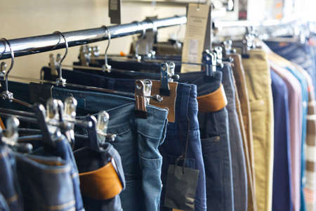 jeans hung on hangers in store for sale photo