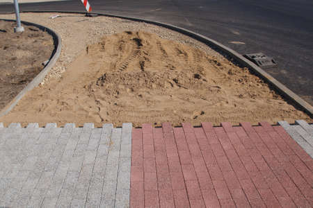 pave: A light gray and red patterned unfinished sidewalk construction site