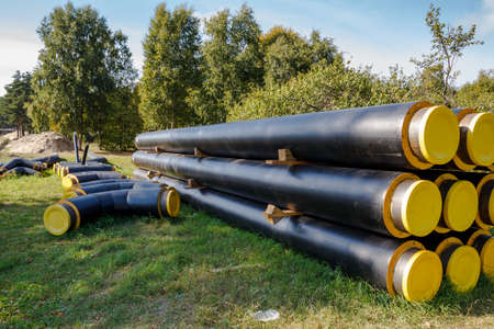A bunch of black and yellow construction pipes layed on the ground photo
