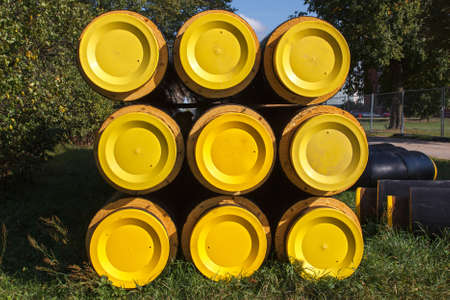 A bunch of yellow and black pipes stacked together photo