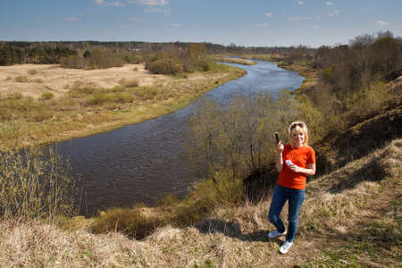 A woman by a river in a unpopulated area playing Geocaching photo