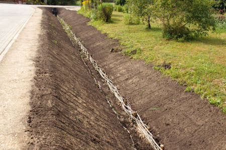 trenching: A trench by a road in a rural area Stock Photo