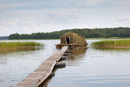 a house with a straw: Straw house in water used as exotic hotel