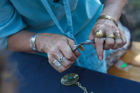 craftman: A craftswomen working with a metal coin. making ethnic jewelry.