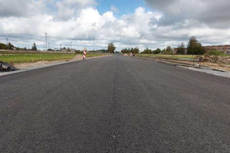 suburban: A newly paved asphalt road in a suburban area