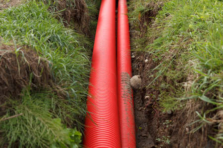 trench: A pair of red cable pipes in a trench