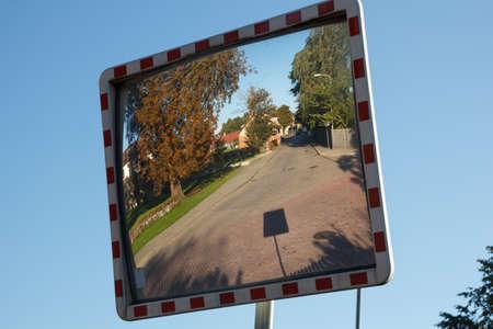 convex: A convex mirror street sign on a road