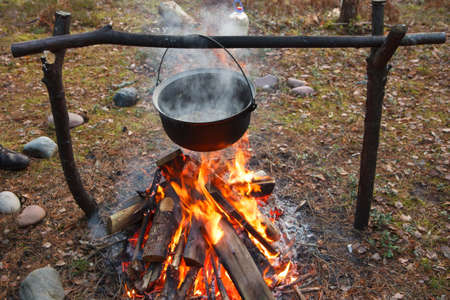camp: A cooking pot being used on a fireplace in a forest Stock Photo