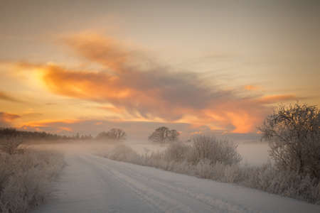 beautiful scenery: A beautiful scenery with a winter road and a sunset