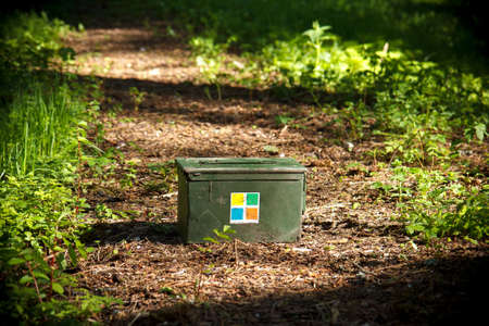 A green Geocaching ammo container in the forest Stockfoto