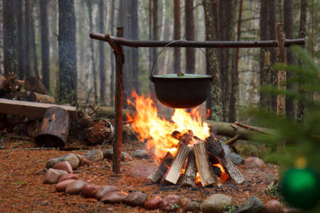 Boiling in the forest using a cauldron on a fireplace Stock Photo