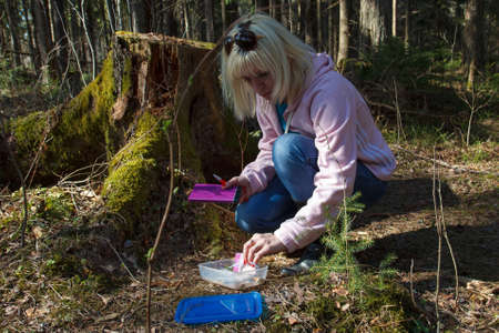 A woman geocaching in a green forest