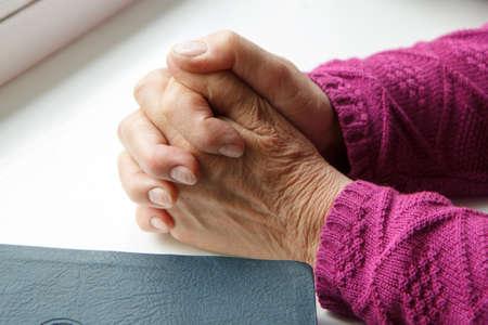 one female: elderly women hands crossed in prayer next to Bible