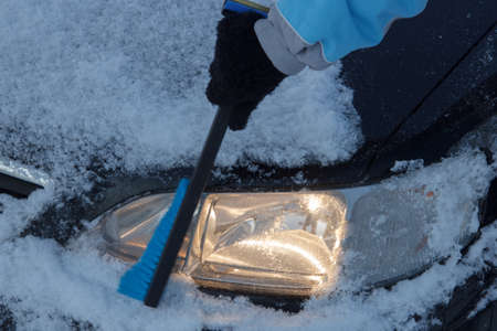 cleared: Snow covered car lights being cleared off